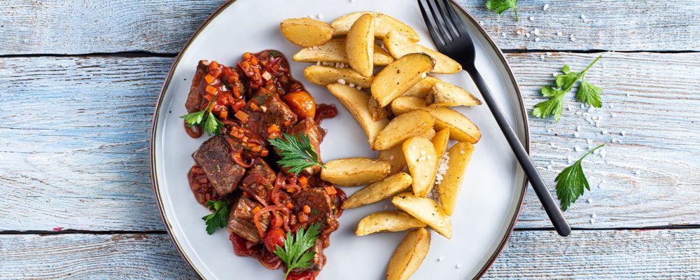 Loomaliha guljašš tomatite ja peterselliga serveeritud koos Pati Parts Garlic kartulilõikutega